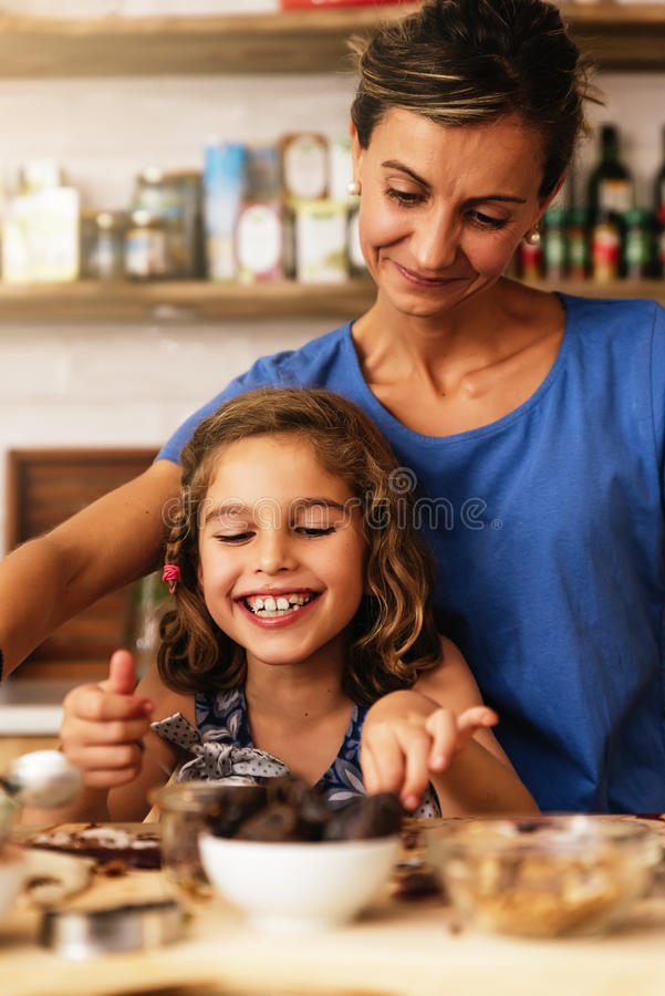 Little girl cooking with her mother in the kitchen. stock photography