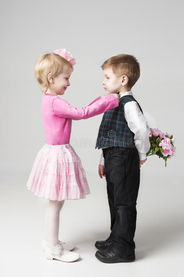 Little girl corrects boy's tie. Young gentleman holding a bouquet of flowers behind his back. Gray background. Studio shot. Romantic relations imitating adults royalty free stock images