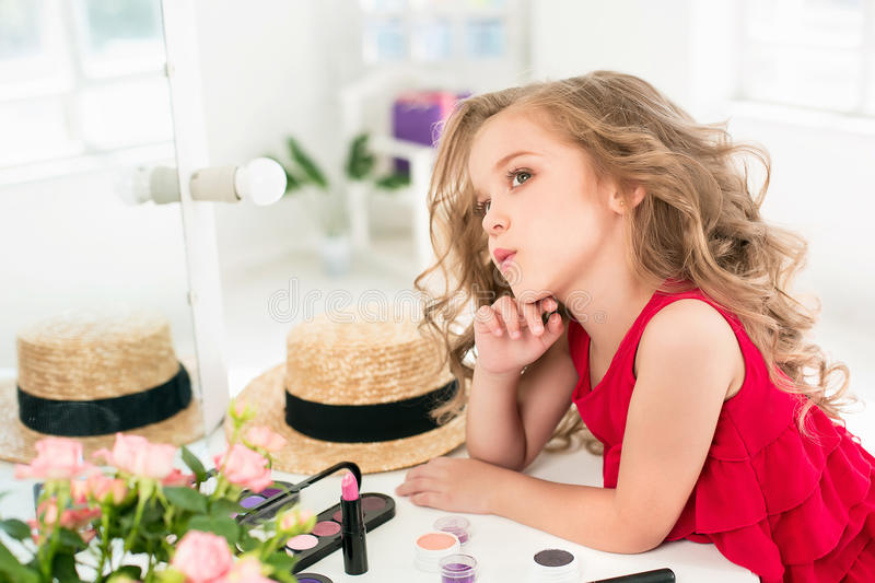A little girl with cosmetics. She is in mother`s bedroom, sitting near the mirror. stock photos