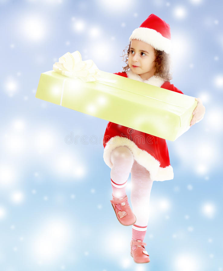 Little girl in costume of Santa Claus with gift stock photo