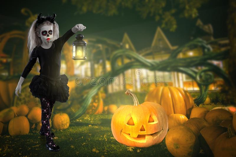 Little girl in a costume of witch posing with pumpkins over fairy background. halloween royalty free stock photography