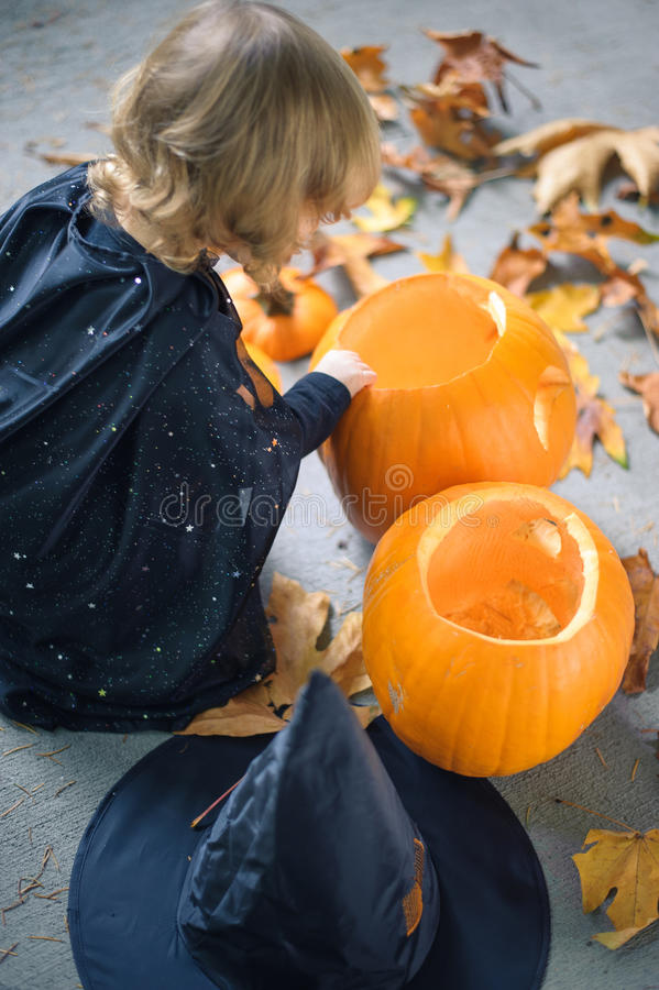 Little girl in a costume of a witch sitting near two pumpkins royalty free stock photography