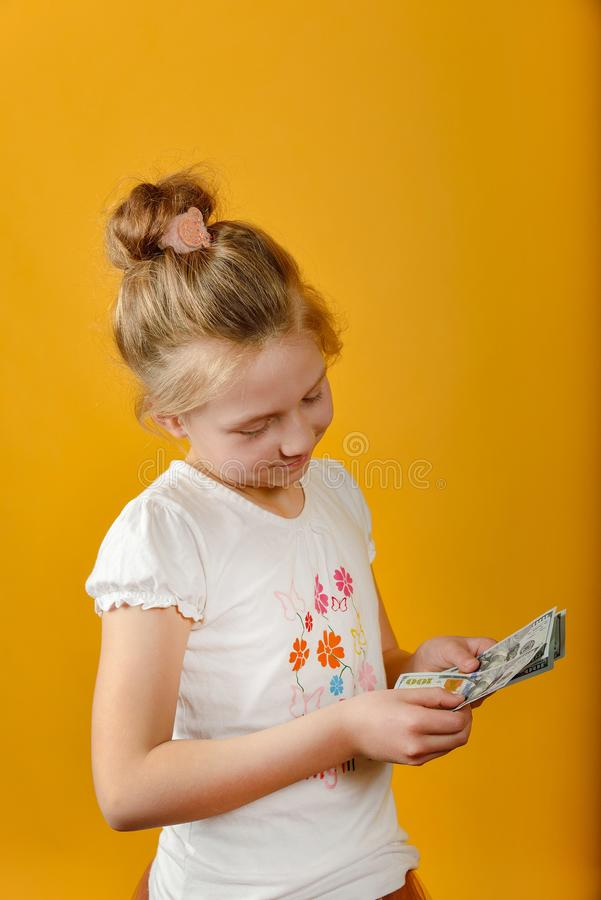 Little girl counts money in hands while thinking about shopping, on yellow background royalty free stock photography