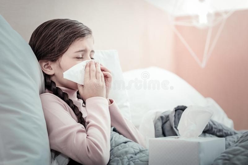 Little girl covering face while sneezing. Keep calm. Sick female person wrinkling forehead and using serviette while blowing nose royalty free stock image