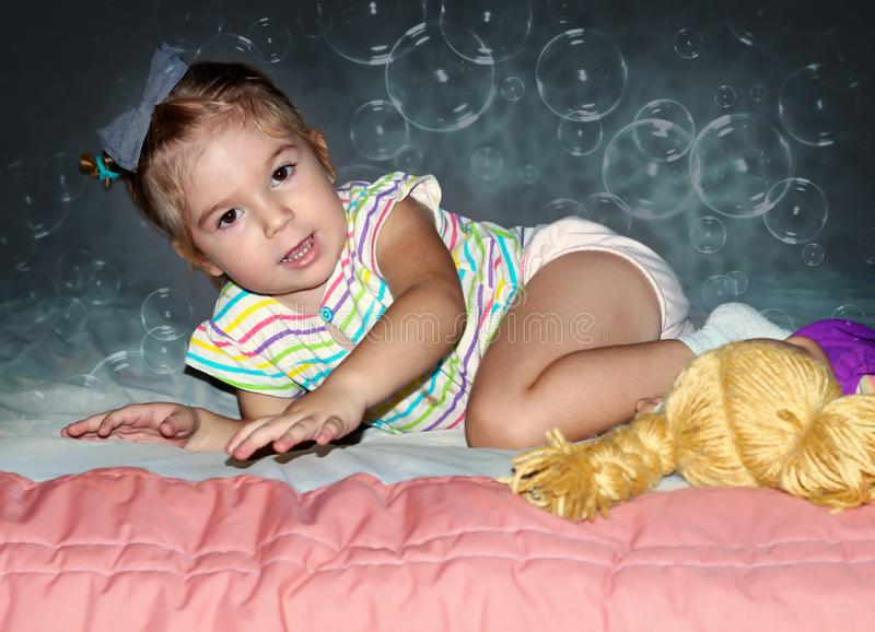 little girl crawling on the bed. stock photo