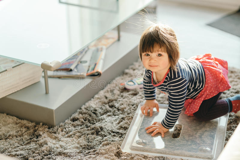 Little girl crawling on the floor in the living room stock photo