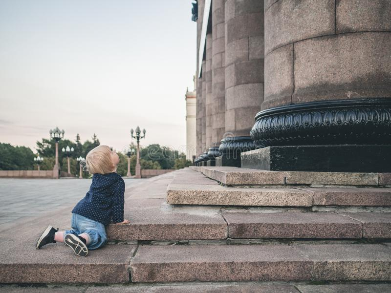 A little girl crawls on her knees along the granite steps of a huge building. Monumental granite columns rise in front stock image