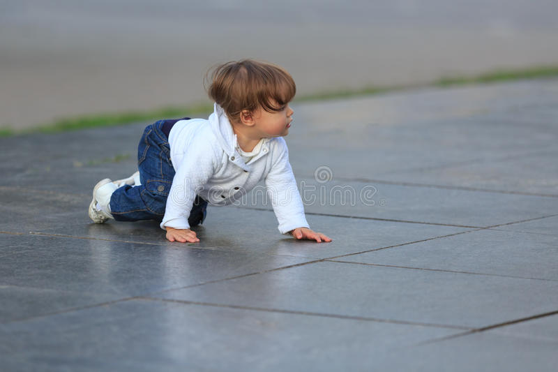 Little girl crawls on marble slabs outdoors in summer stock photos