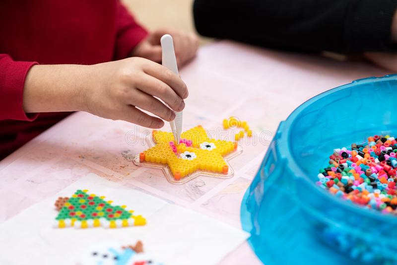Little girl creates pattern using perler beads. Fusible colorful beads. Toy that develops the imagination and creativity of child stock photos