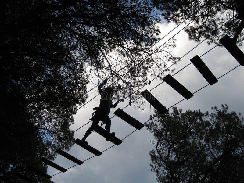 Little girl crosses suspension bridge stock image