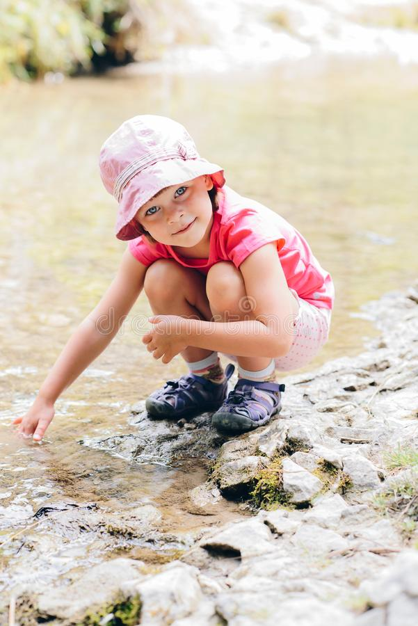 little girl crouches on the bank of the mountain stream stock photos
