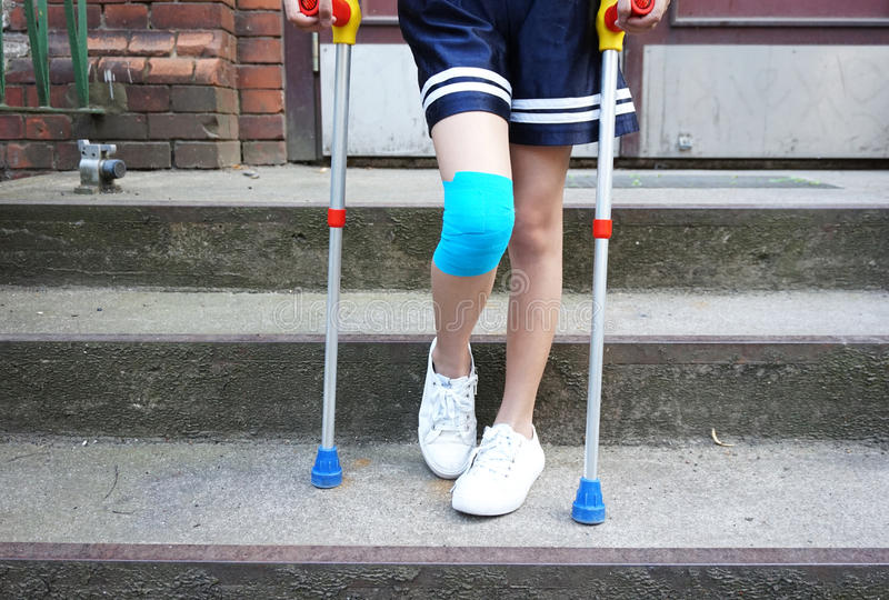 Little girl with crutches at the stair. royalty free stock image