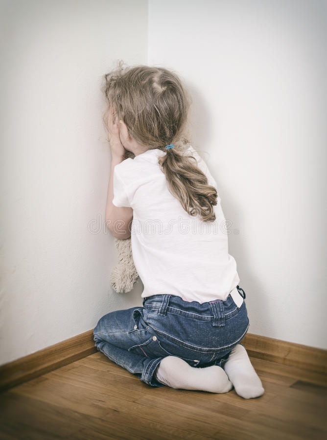 Little girl crying in the corner. stock image