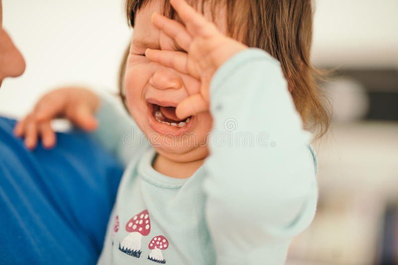 Little girl crying on the daddy hands stock photography