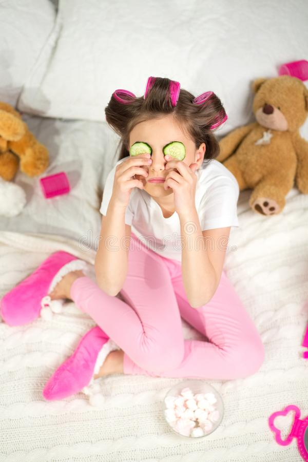 Little girl with cucumber slices on her eyes. stock photos