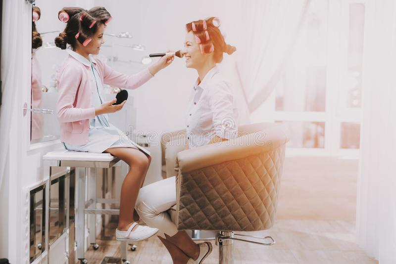 Child does Makeup Smiling Woman in Beauty Salon royalty free stock images