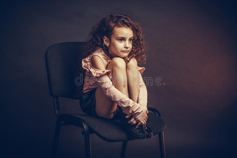 A little girl, with curls in pink blouse and black shorts, sits on an office chair with her feet on her face, hurt, unhappy. A little girl, with curls in a pink royalty free stock photos