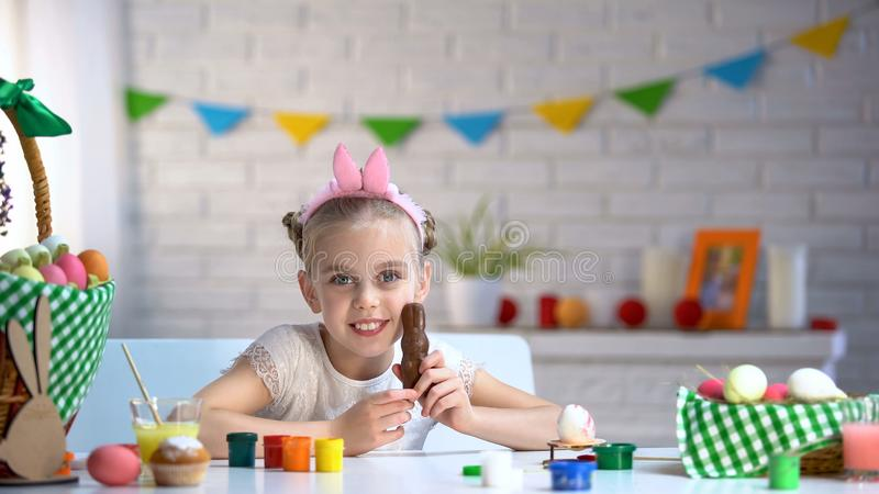 Little girl in cute headband smiling and posing for camera with chocolate bunny stock photo