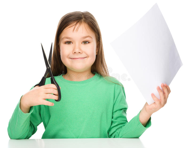 Little girl is cutting paper using scissors. While sitting at table, isolated over white stock photography