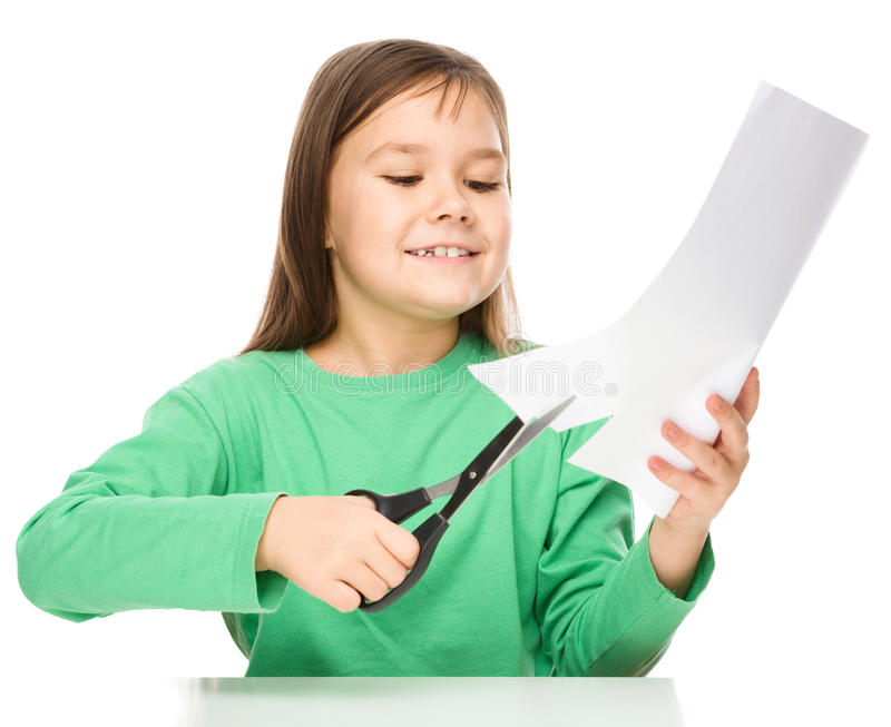 Little girl is cutting paper using scissors. While sitting at table, isolated over white royalty free stock photo