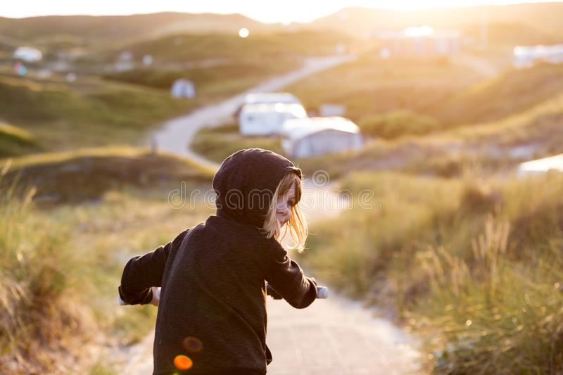 Little girl cycling in campsite. Texel, Holland stock photos