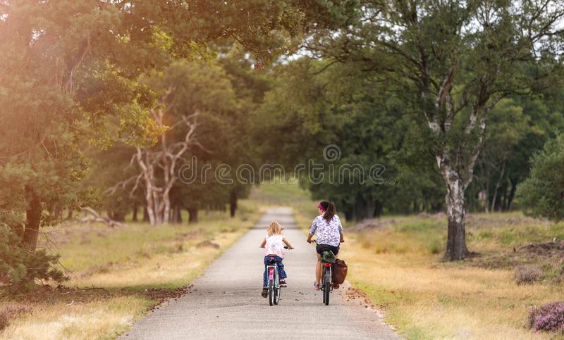 Little girl cycling with her mother. In Holland stock image