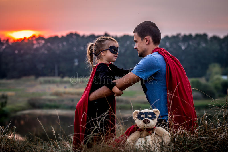 Little girl with dad dressed in super heroes, happy loving family. Father and daughter playing outdoors, family values royalty free stock photo