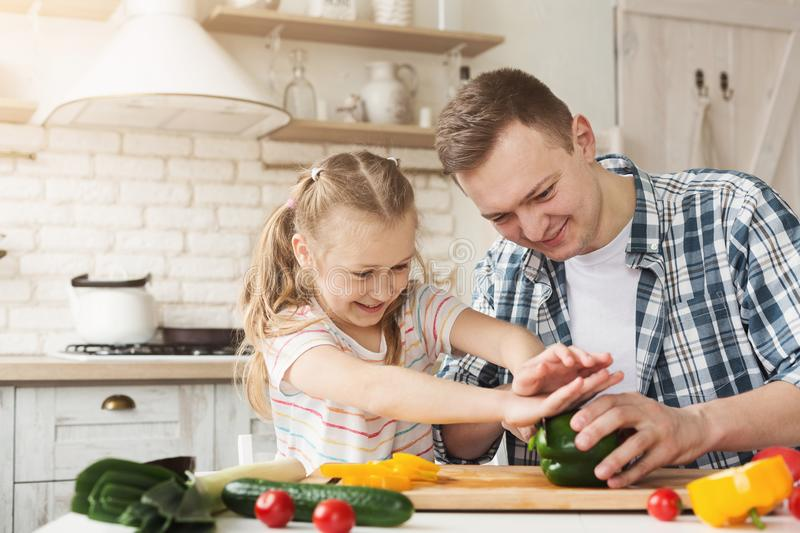 Little girl and dad having fun while cooking in kitchen stock photography