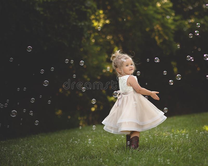 Little girl dancing in bubbles royalty free stock photography