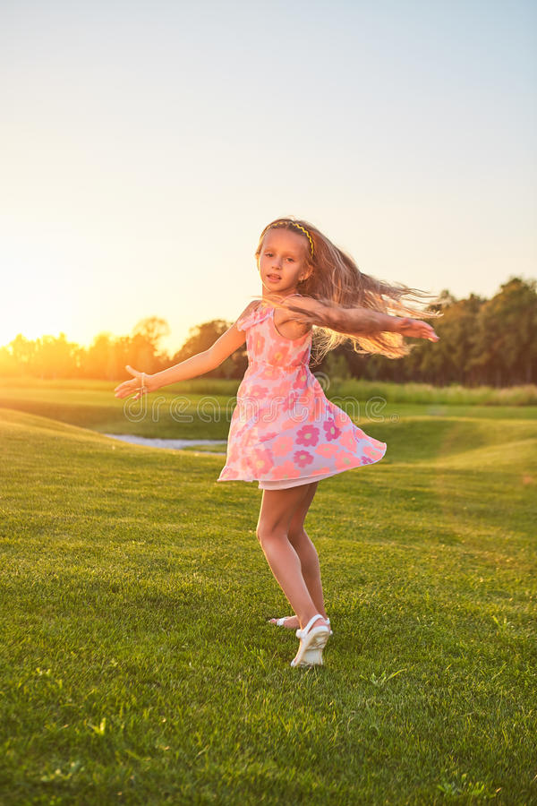 Little girl dancing on grass. stock photography