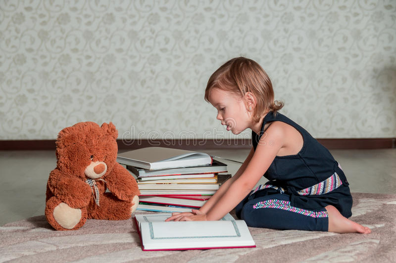 Little girl in dark blue dress reading book sitting on the floor near teddy bear. Child reads story for toy. A little girl in a dark blue dress reading a book royalty free stock photo