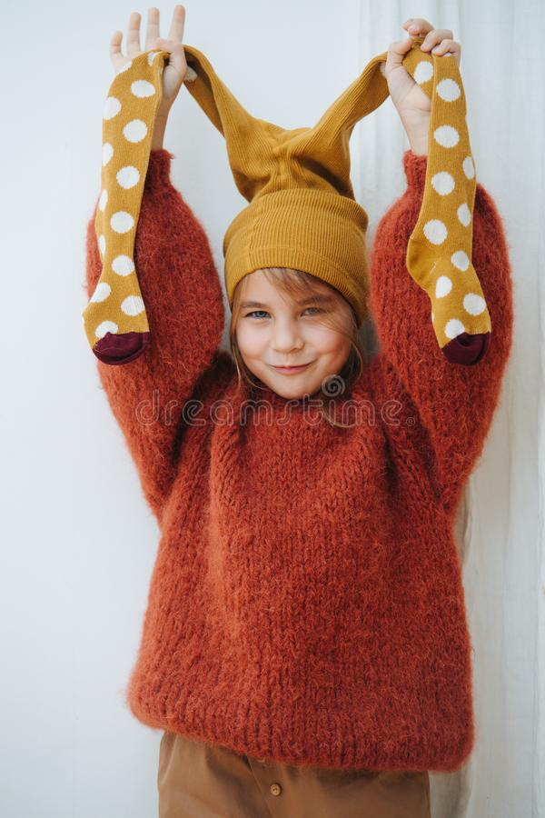 Little girl in dark orange knitted sweater with tights on her head stock photo