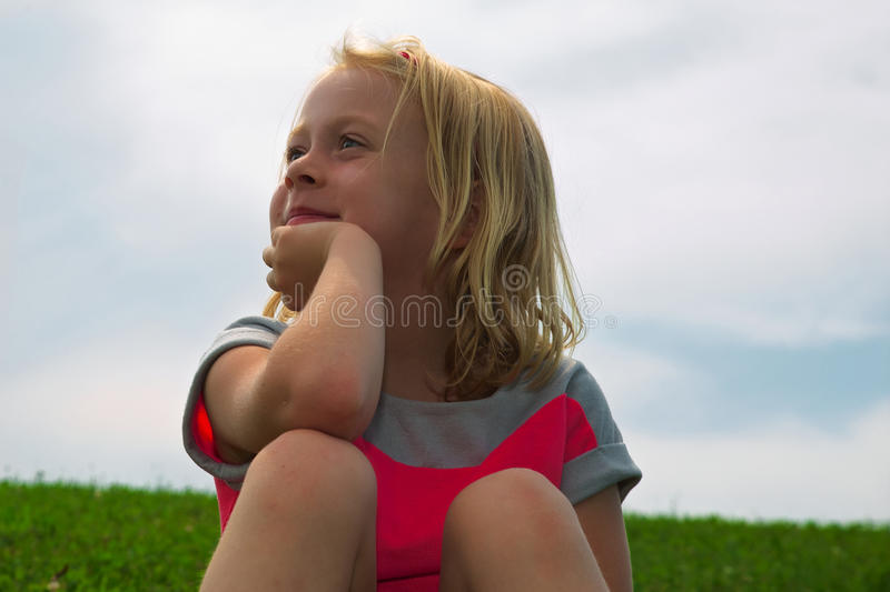Little Girl Daydreaming. Little girl staring off into the distance daydreaming stock photo