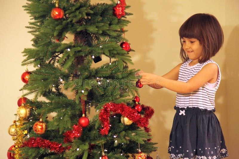 Little girl decorates Christmas tree stock image