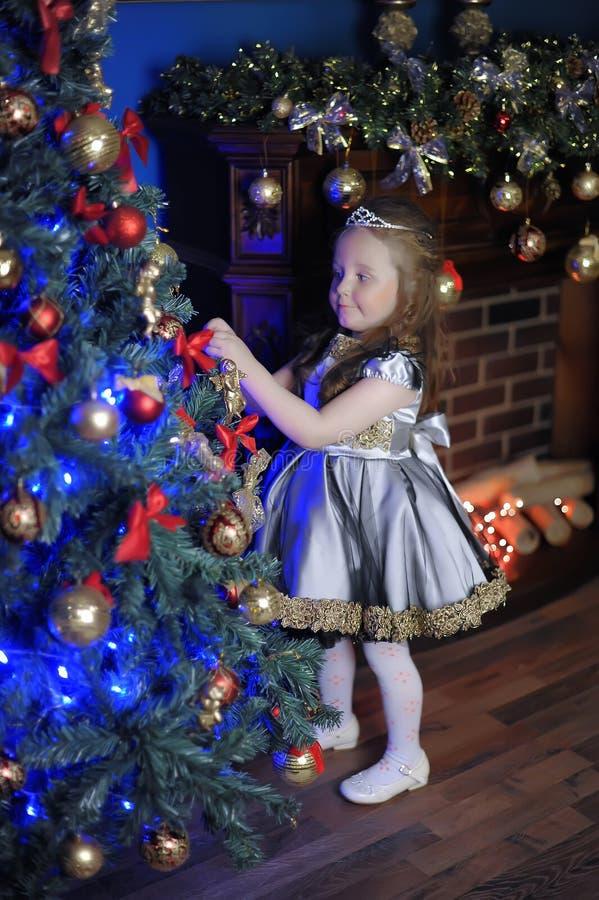 Little girl decorates  Christmas tree royalty free stock photo
