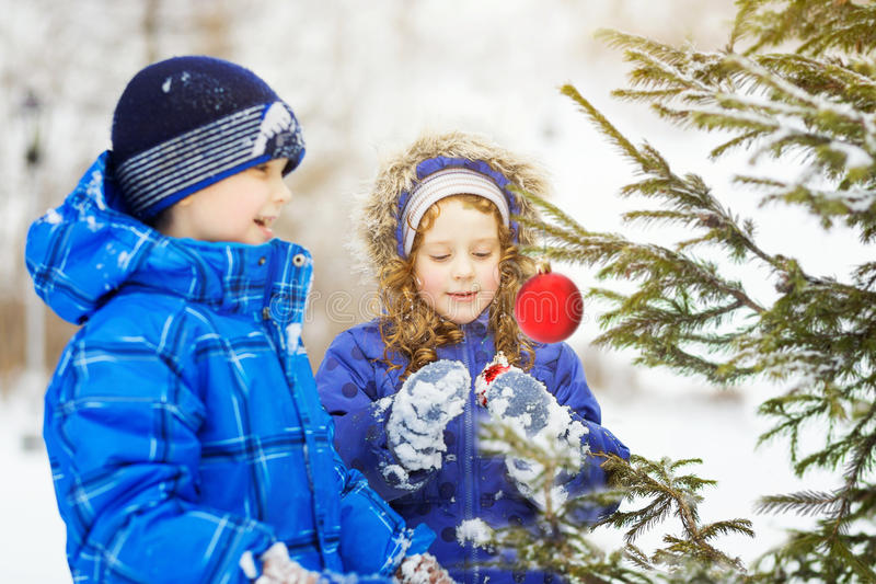 Little girl decorates the Christmas tree. stock image