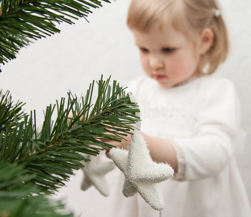 Little girl decorating Christmas tree royalty free stock photos