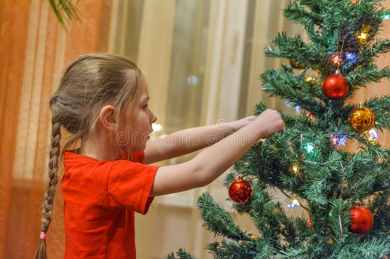 Little girl decorating a Christmas tree. Adorable little girl decorating a Christmas tree with colorful glass baubles at home stock image