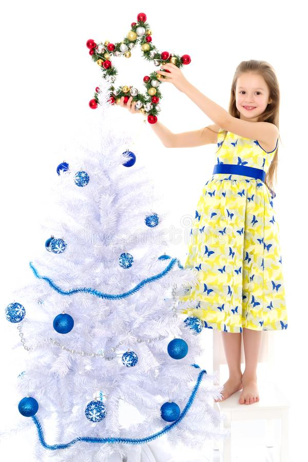 A little girl is decorating a Christmas tree. royalty free stock images