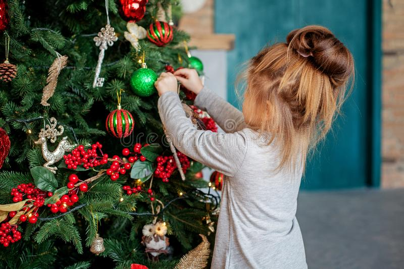 A little girl is decorating a Christmas tree in the house. The concept of a Merry Christmas, holiday, family royalty free stock images