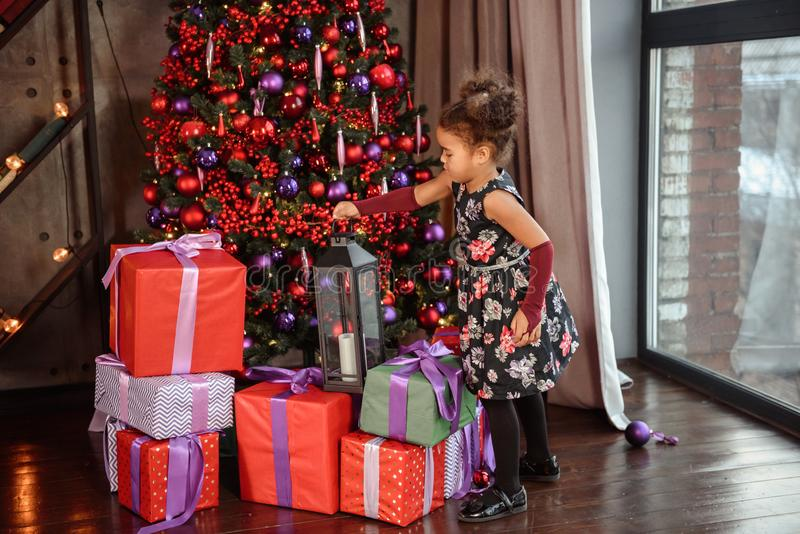 Merry Christmas! Cute little child girl is decorating the Christmas tree stock images
