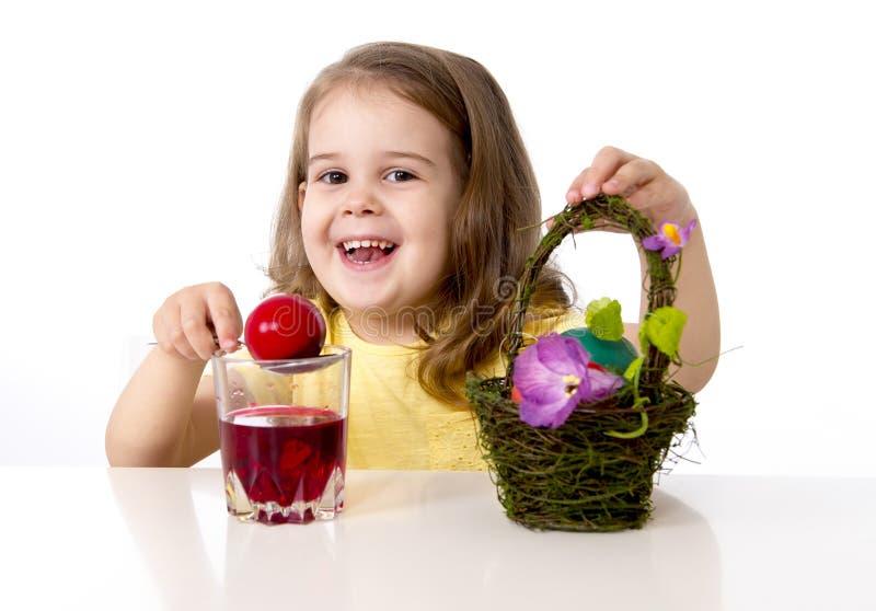 Little girl decorating traditional Easter egg. Happy sweet little girl dying and painting traditional Easter eggs in vivid colours with paint and dye stock images
