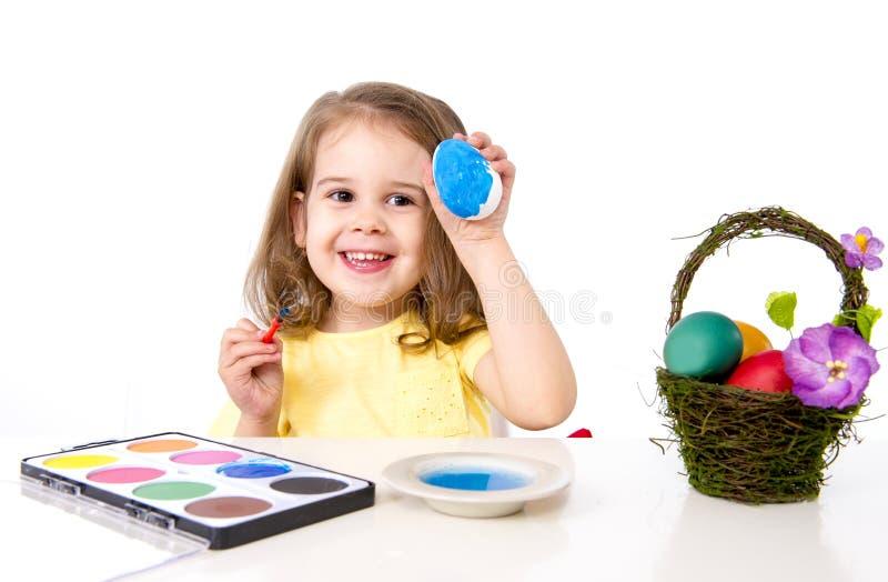 Little girl decorating traditional Easter egg. Happy sweet little girl dying and painting traditional Easter eggs in vivid colours with paint and dye royalty free stock image