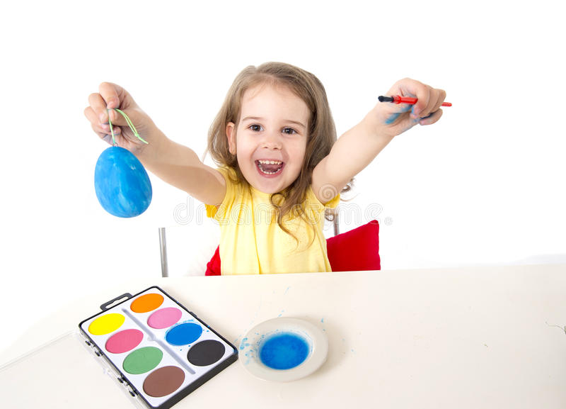 Little girl decorating traditional Easter egg. Happy sweet little girl dying and painting traditional Easter eggs in vivid colours with paint and dye stock photography