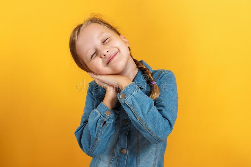 Little girl in a denim shirt on a yellow background. The child closed her eyes and laid her head on folded palms stock photography