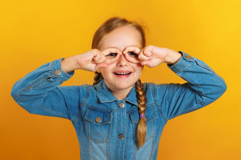 Little girl in a denim shirt on a yellow background. The child has fun and makes glasses out of fingers stock photo