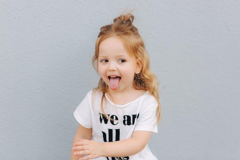 Little girl deride. Beautiful blond hair female child stock photo