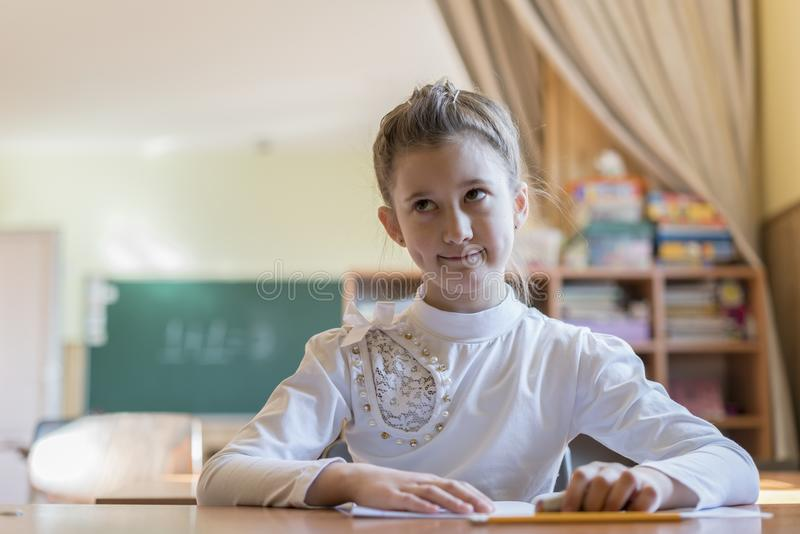 little girl at the desk is writing. education and school concept - little student girl writing in notebook at school stock images
