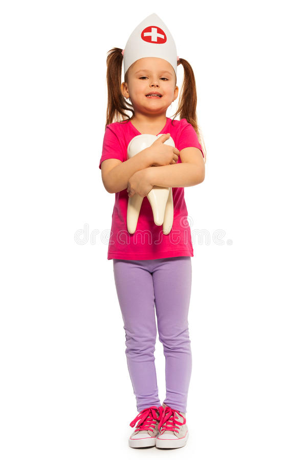 Little girl in doctor cap holding big tooth model. Little girl in doctors cap holding big tooth model, isolated on white stock photography