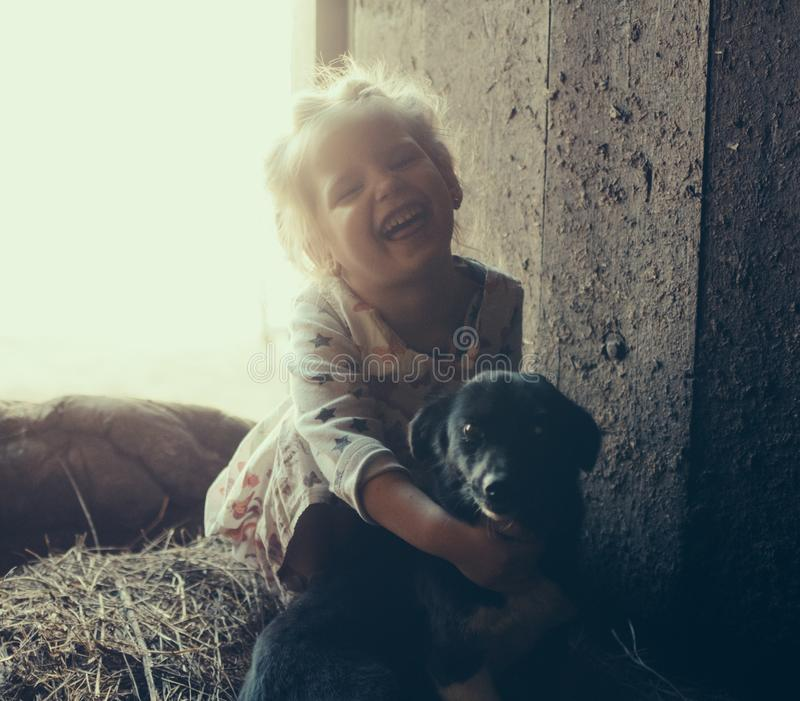 Little girl with a dog in a barn on straw royalty free stock photo